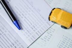 Желтый автомобиль и ручка игрушки помещенные на банковской книжке на предъявителя банка на взгляд сверху Стоковая Фотография RF