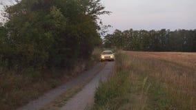 Желтый автомобиль управляет вдоль дороги к полю видеоматериал