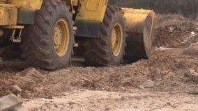Желтый большой затяжелитель конструкции выравнивает кусок земли для конструкции и собирает землю в ведре, индустрию видеоматериал