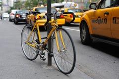 Желтый велосипед и желтые такси стоковые изображения rf