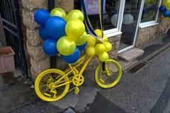 Желтый велосипед, с голубыми и желтыми воздушными шарами стоковые фото