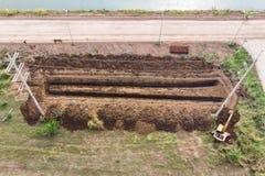Желтый выкапывать backhoe бороздит на почве в сельскохозяйственном районе стоковые изображения rf
