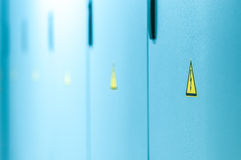 Желтый высоковольтный знак на голубых дверях. Стоковые Фото