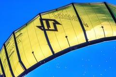 Желтый змей всадников kitesurf витая в воздухе на предпосылке голубого неба в солнечном свете Kitesurfer едет змей в ветре Закрой стоковое фото