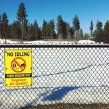 Желтый знак на проволочной изгороди с снежными землей и травой в парке поверните выключенный двигатель Улучшите качество воздуха стоковое изображение