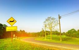 Желтый знак уличного движения при олени скача внутри знака и имеет ` скрещивания живой природы предосторежения ` сообщения на дор Стоковые Фотографии RF