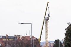 Желтый кран конструкции будучи собиранным используя кран автомобиля Силуэт работника достигая для кабины crain для того чтобы при Стоковое Фото