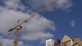 Желтый кран конструкции на фоне облачного неба дневного времени акции видеоматериалы