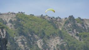 Желтый параплан летает против предпосылки зеленых скалистых крымских гор видеоматериал