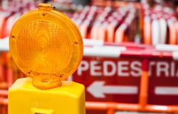 Желтый предупредительный световой сигнал и красные барьеры улицы Стоковая Фотография
