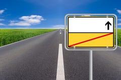 Желтый пустой знак улицы с улицей в предпосылке стоковое фото rf