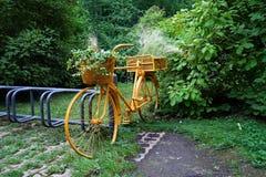 Желтый старый велосипед в парке с цветочными горшками стоковое изображение