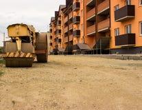 Желтый старый paver на предпосылке дороги, подготовленной для класть асфальта и нового дома стоковое изображение