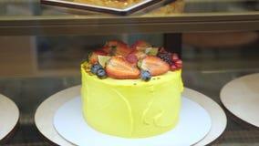 Желтый торт со свежими ягодами и сливк в витрине пекарни на стеклянной полке акции видеоматериалы