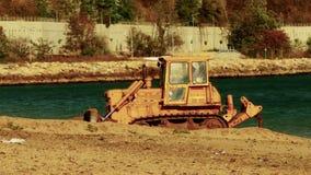 Желтый трактор бульдозера поднимает песок на пляже видеоматериал