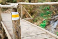 Желтый туристский знак на деревянном мосте стоковые изображения