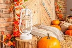 Желтый цвет осени выходит, тыквы, осень, бочонок, лампа, солома, деревянная дверь на предпосылке Стоковые Изображения