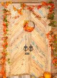 Желтый цвет осени выходит, тыквы, осень, солома, деревянная дверь на предпосылке Стоковая Фотография