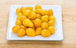 желтый цвет томатов плиты груши вишни белый Стоковые Фотографии RF