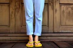 желтый цвет flops flip Ноги и ноги женщины нося желтые сандалии стоя на деревянном поле и деревянной стене Стоковые Фото