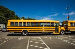 Желтый школьный автобус припаркованный в серии Стоковые Изображения
