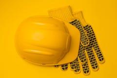 Желтый шлем конструкции на желтой предохранении от предпосылки и защитных перчаток, головы и руки, концепции, взгляд сверху стоковые фотографии rf