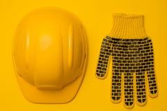 Желтый шлем конструкции на желтой предпосылке и одном защитной предохранении от перчатки, головы и руки, концепции, взгляд сверху стоковые фотографии rf