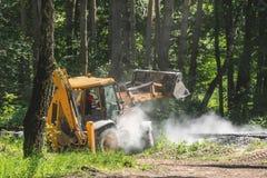 Желтый экскаватор льет гравий на конструкции железной дороги в лесе Стоковые Изображения