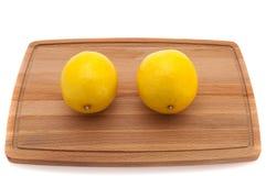 Желтый яркий сочный лимон 2 на деревянной разделочной доске Стоковые Фото
