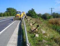 Желтый backhoe на дороге стоковое изображение rf
