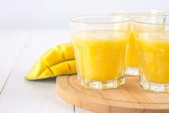 Желтый smoothie манго, банана и апельсина на белые деревянные животики Стоковые Фотографии RF