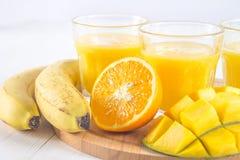 Желтый smoothie манго, банана и апельсина на белые деревянные животики Стоковые Изображения RF