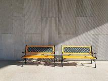 2 желтых винтажных стенда конструировали с светом утра от стороны в раннем утре на текстурированной предпосылке бетонной стены Стоковые Изображения RF