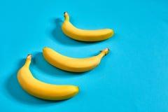 3 желтых зрелых банана на голубой предпосылке с космосом для текста или дизайна Взгляд сверху Стоковые Фотографии RF