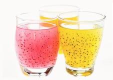 2 желтых и питья одних розовых плодоовощ с семенем базилика в стеклах, изолированных на белизне Стоковое Фото