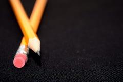 2 желтых карандаша на предпосылке темной черноты запачканной stationery Инструмент офиса владение домашнего ключа принципиальной  Стоковые Фотографии RF