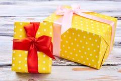 2 желтых подарочной коробки, деревянная предпосылка Стоковая Фотография