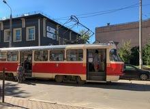 Желт-красный трамвай города приехал на стоп стоковое изображение rf