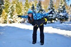 Женатая любящая пара околпачивая вокруг в снежном лесе на солнечной зиме стоковое изображение rf