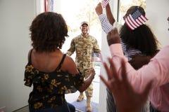 Жена и семья ждать парадным входом для дома молодого Афро-американского солдата возвращающ, конца вверх стоковые изображения rf