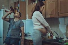 Жена моет блюда, спиртной супруга стоковое изображение rf