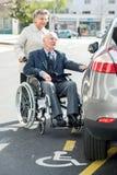 Жена нажимая супруга инвалидов к автомобилю Стоковое фото RF