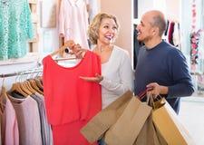 Жена радостного старшего супруга помогая очаровательная для того чтобы выбрать платье стоковая фотография rf