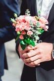 Жених в синем костюме держит букет свадьбы сделанный роз Стоковое Изображение