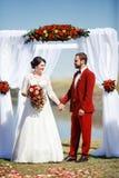 Жених и невеста во время ceremon свадьбы, свода цветет outdoors Стоковое фото RF