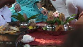 Жених и невеста выполняет обряд рядом с аксессуарами сток-видео