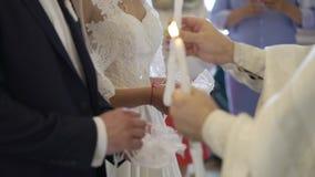 Жених и невеста держа свечи в церков на церемонии акции видеоматериалы