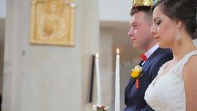 Жених и невеста держа в руках освещенных свечи видеоматериал