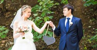 Жених и невеста держа знак сердца форменный Стоковые Изображения RF