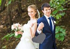 Жених и невеста держа знак сердца форменный Стоковое Изображение RF